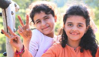 Zwei geflüchtete Mädchen zeigen das Peace-Zeichen